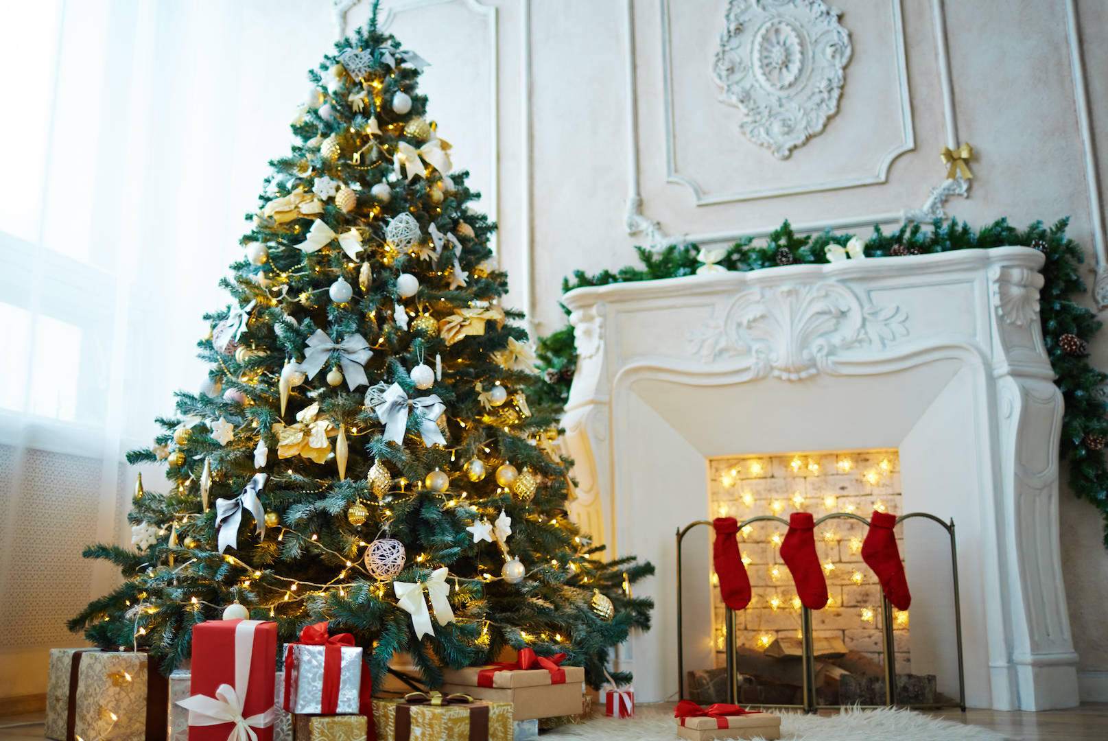 Ok decorated xmas tree packages with gifts and red socks on fireplace in the room voltagebd Images